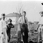 "Myron Edward ""John"" Ames with sons ""Phil"" and ""Bob"" and friend in front of their home at 6th Avenue and F Street, ca. 1933.  The Anchorage Public School is shown in the background."