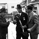 Bob Atwood shortly after his arrival in Anchorage (on right).  Atwood is talking to F. C. Hanson, an engineer with the Alaska Railroad, and Jim Farley, the U. S. Postmaster General, in front of the Anchorage Post Office on Fourth Avenue.