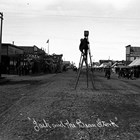 Alberta Pyatt took this photograph of Fourth Avenue, Anchorage,  around 1916 or 1917.  Visible on the right, just beyond the awnings, is the sign for the Union Cafe, where Balios worked as a cook.  Artist and photographer Sydney Laurence stands on a ladder in the center of the street to use a huge tripod supporting a large camera.