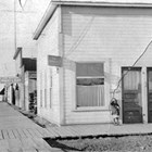U.S. Commissioner' office, 5th Avenue and E Street, Anchorage, 1916-1917.  Leopold David was U.S. Commissioner during his first year in Anchorage, before becoming a lawyer in private practice. Daughter Caroline David stands by the door.