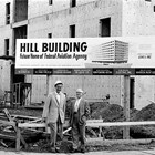 "Donald ""Don"" and Harry Hill in front of  the Hill Building, 6th Avenue and G Street, Anchorage, during construction, ca. 1961."