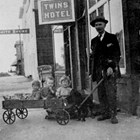 John Casey McDannel with the twins (Mary and Helen), right, and unidentified child, left, in wagon, 1918.