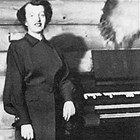 Evangeline Rasmuson Atwood, standing at the organ in her home in the Turnagain neighborhood of Anchorage, February 6, 1954.