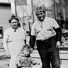 "Lauretto ""Laura"" and Gaetano ""Joe"" Ionnone (Reno) with one of their grandchildren, in front of their store at 4th Avenue and C Street, Anchorage."