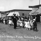 Anchorage elementary school students marching in a parade, Anchorage, 1915 or 1916.  The woman in the dark clothing walking alongside them has been identified as Orah Dee Clark.