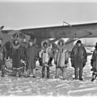 A group of men, probably pilots or employees of Star Airlines, with one of the company airplanes. Most of the men wear Alaska Native cold weather clothing, including reindeer fur parkas, reindeer or seal fur mukluks, and moosehide gauntlets.