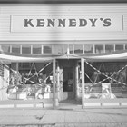 A view of Kennedy's clothing store with patriotic decorations, possibly to celebrate Washington and Lincoln's birthday or the 4th of July.  The photograph was taken some time after James Kennedy's death in 1934, after his brother and partner Daniel moved the store across 4th Avenue to this location.