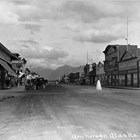 A view facing east on Fourth Avenue in Anchorage before 1934.  On the left side of the photograph is a sign for Kennedy's Clothing, which was run by brothers Daniel and James Kennedy.  After the death of James in 1934, brother and partner Daniel moved the store across Fourth Avenue.