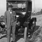 Sydney Laurence standing in front of a Model T Ford in 1928. There are a number of photographs of him with automobiles, although several stories indicate he was not a good or enthusiastic driver.  Early Anchorage settler Nellie Brown took this photograph and later recollected that he let her drive him around in the automobile, and later the Model T  became Nellie's.