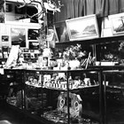Sydney Laurence sold his paintings through a number of outlets.  In Anchorage it was Hewitt's Drug Store; in Juneau, it was the Nugget Shop.  This photograph of the Nugget Shop shows some of his paintings on the walls.