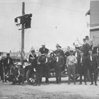 "Anchorage Fire Department, 1924.  Thomas ""Tom"" Bevers is the man standing third to the right of the vehicle's front tire.  At the time this photograph was taken, Bevers was a paid firefighter in a mostly volunteer fire department."