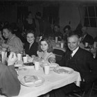 James Delaney, his wife Nancy, and one of their two daughters at a dinner and dance in the Army Recreational Hall at Fort Richardson on January 13, 1945.