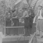 Anchorage mayor James Delaney (second man on the left) at the Anchorage Light and Power Company's Eklutna River Gorge hydroelectric dam around 1930, just after Anchorage began getting its power through this company.  The third figure from the left is Oscar Gill, who was a city councilman during the three years that Delaney was mayor, and succeeded Delaney in the mayor's office in 1932.