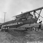 A Travel Air 7000, one of the first two planes owned by Anchorage Air Transport, a company owned by a number of Anchorage businessmen in the late 1920s.  The plane often landed or took off from the Anchorage Park Strip, which was used as a landing field before Merrill Field was built.  The figure working the propeller has been identified as pilot Russel Merrill.