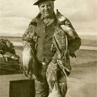 "Christian ""Chris"" Eckmann with the waterfowl that he shot in Cook Inlet.  Hunting waterfowl in the fall was a major activity in early Anchorage, with groups of friends chartering boats from the 'mosquito' fleet to take them to the west side of Cook Inlet to hunt. A brief note in the Anchorage Daily Times on August 30, 1926, reads: ""Duck hunting is the main topic of discussion about town and will probably hold the center of interest for some time."""