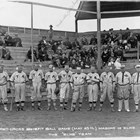 "Christian ""Chris"" Eckmann, the fifth man from the right, playing for the Elks against the Masons on May 25, 1918.  Eckmann holds a baseball bat in his right hand, running down his right leg.  Baseball was very popular in early Anchorage; the ballpark was where the Anchorage Museum now stands."