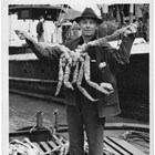 Henry Emard with a large king crab, ca. 1940-1950.