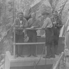 Oscar Gill (third from the left) and several others inspect the hydroelectric dam on the Eklutna River below Eklutna Lake,  ca. 1930.  The hydroelectric project came on-line in 1929, providing cheaper power for Anchorage and the Alaska Railroad yards than the Alaska Railroad's old coal burning power plant.  To Gill's left is James Delaney, who preceded Gill as mayor of Anchorage.