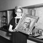 Mildred Hamill holding a portrait of prominent Anchorage artist Sydney Laurence, the only known portrait for which Laurence actually sat.  According to Hamill, Laurence asked that she do his portrait and he sat for her every morning for a week.  The painting is currently in the collection of the Anchorage Museum at Rasmuson Center.