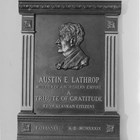 "Bust of Austin E. ""Cap"" Lathrop.  From front, the inscription reads:  ""Austin E. Lathrop, builder of a northern empire.  A tribute to gratitude from Alaskan citizens.  Fairbanks A.D. MCMXXXIX.""  1939.  The bust was modeled by Piertro Vigno, a Fairbanks artist, from a photograph.  The plaque was placed in the studio of radio station KFAR, Fairbanks, and unveiled during dedication ceremonies held on October 2, 1939."
