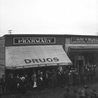 Exterior view of Z.J. Loussac's first drug store in Anchorage, albeit obscured by a parade.