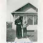 Father O'Flanagan standing before the Catholic rectory next to Holy Family Church in Anchorage in 1941.  The name of the boy is unknown.