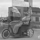 "Wiiiam A.C. ""Lucky"" Baldwin became incapacitated later in life, and was known for riding around Anchorage in his motorized wheelchair.  Here he has the wheelchair decorated for a parade during the mid to late 1930s, touting President Franklin Roosevelt's New Deal program."