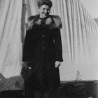 After World War II, Lorene Harrison worked as the 'welcome hostess' who brought gifts from Anchorage merchants to newcomers.  Here she stands in front of a tent that was the first Anchorage home of a young couple who recorded that Harrison visited them several times and brought Pepsi Cola, box candy, hand lotion, and a bouquet of carnations.