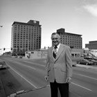 "Walter ""Wally"" Hickel stands in front of his Hotel Captain Cook in May 1974, before the third tower was built where the Bering Sea Original store stood."
