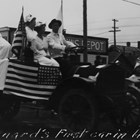 "Another view of Joseph ""Joe"" Spenard driving in a parade, this time touting the American Red Cross, possibly during World War I in 1917 or 1918.  Whether he had the first automobile or truck in Anchorage is less certain."